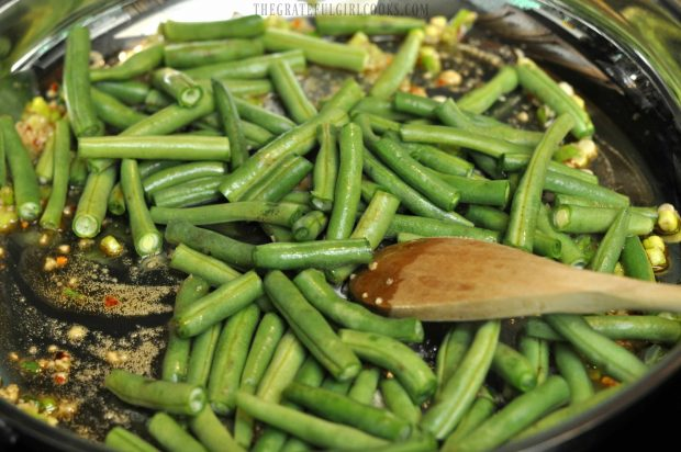 Green beans are added to the skillet.