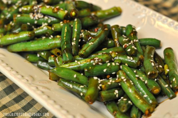 The spicy green beans are sprinkled with sesame seeds and served.