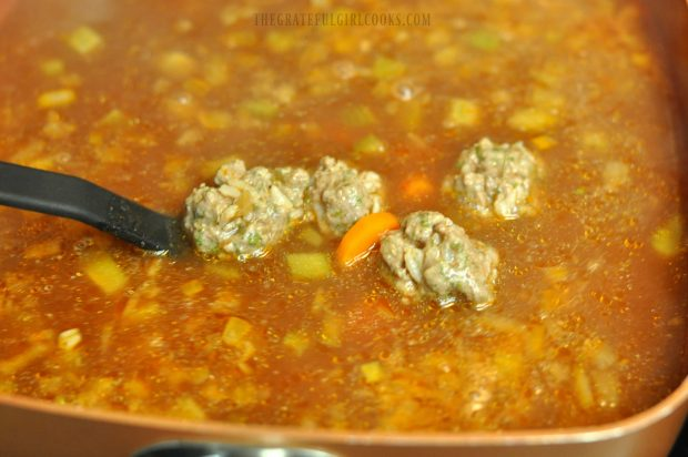 Stirring meatballs in soup
