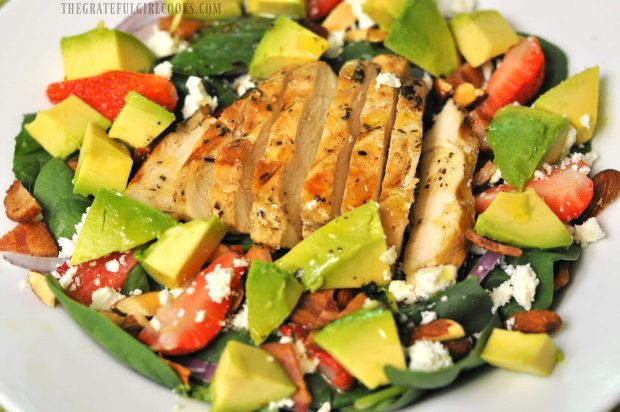 Avocado chunks added to spinach salad, along with dressing.