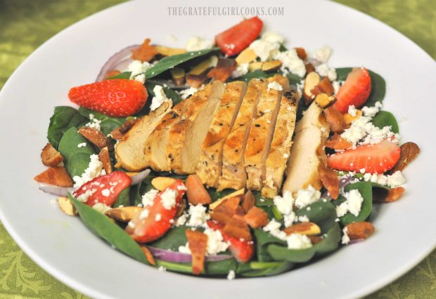 Chicken breast is sliced then served atop the spinach salad with avocado and strawberries.