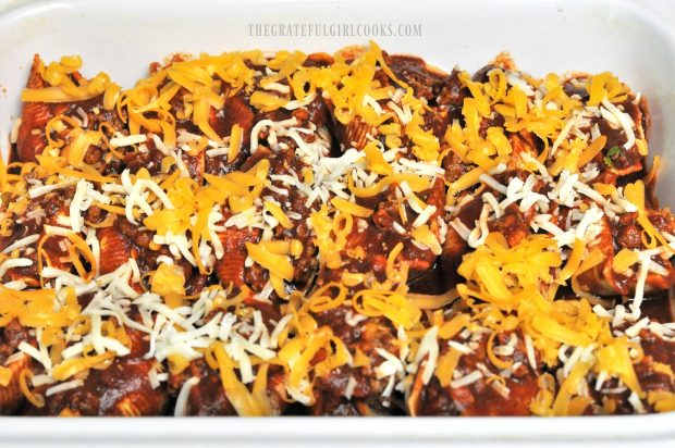 Mexican Stuffed Pasta Shells are covered with grated cheese before baking.