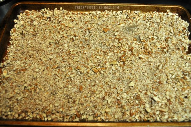 Chopped pecans are roasted in oven for pecan pie truffles.
