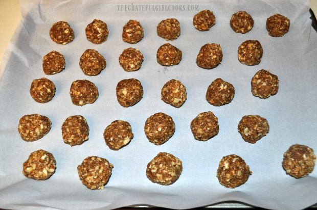 Pecan Pie Truffles are shaped into balls, then placed on parchment paper lined pan to refrigerate.