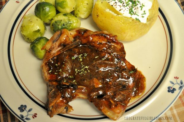 Smothered pork chops on plate with baked potato and brussel sprouts on the side.