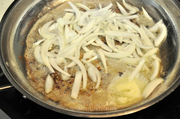 Onion slices are cooked in butter for smothered pork chops.
