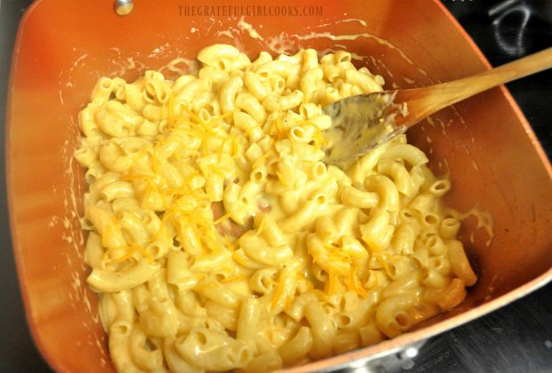 Macaroni and cheese is stirred well, to coat everything with sauce.