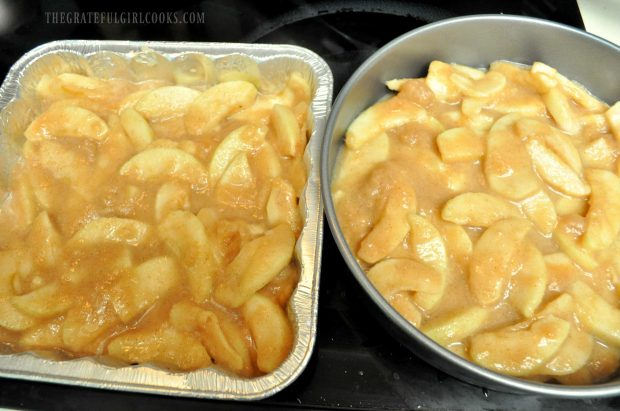 Apple pie filling is spread into baking pans.