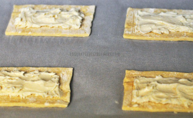 Cream cheese filling is placed onto puff pastry rectangles.