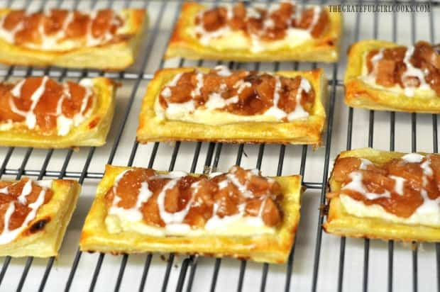 Apple cream cheese pastries are drizzled with powdered sugar glaze.