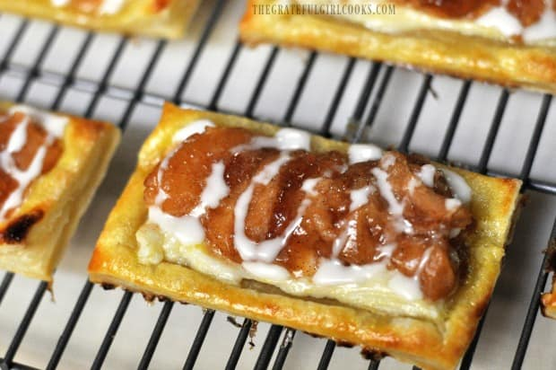 Close up photo of apple cream cheese pastries with glaze, on wire rack.
