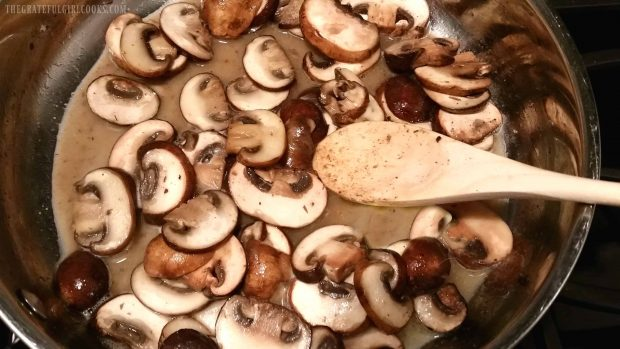 Mushrooms and wine cooking in metal skillet with a wooden spoon