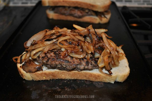 Patty melt is piled high with cooked onion slices.