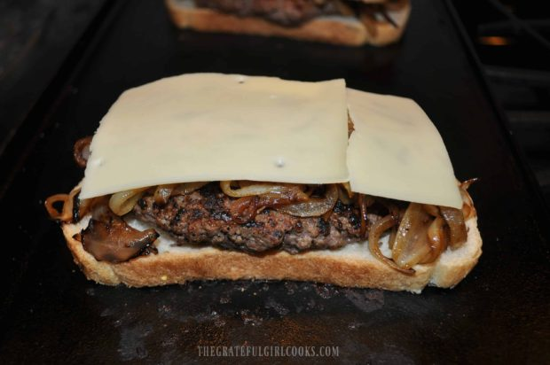 Swiss cheese slices are placed on top of onions on patty melt.