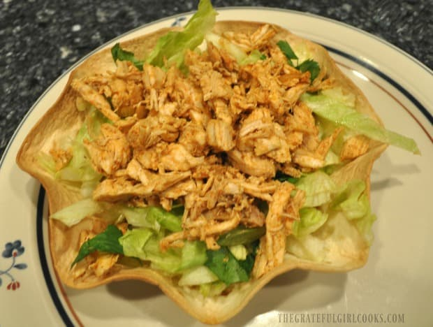 Seasoned chicken in tortilla taco bowl