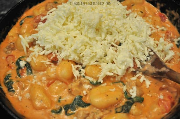 Mozzarella cheese added to skillet with creamy sausage gnocchi