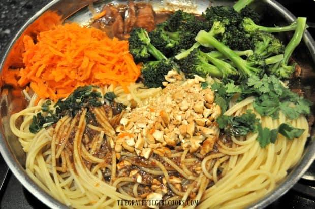 Noodles, hoisin pork, carrots and broccoli in skillet