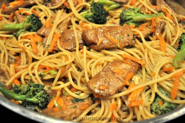 Close up of pork slices, broccoli, carrots and noodles in skillet