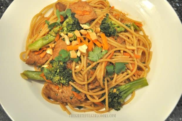 Hoisin pork, noodles and broccoli served in white bowl