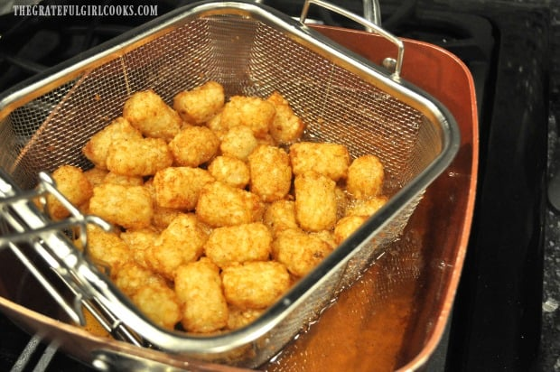 Golden brown tater tots are removed from cooking oil