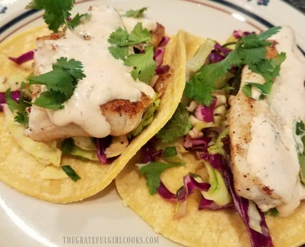 Two grilled fish tacos, with slaw and Baja sauce, on plate