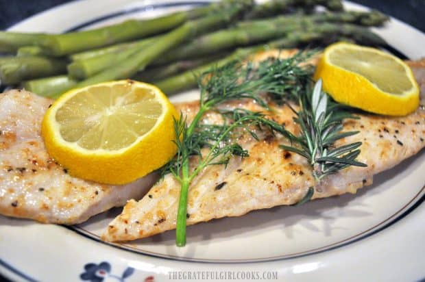 Pan-seared fish with dill, rosemary and lemon slices, on plate with asparagus.