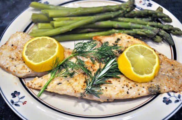 Pan-seared rockfish with lemon and herbs on plate with asparagus