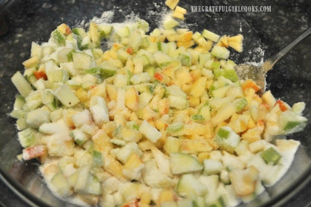 Diced apples for muffins are coated with sugar in bowl