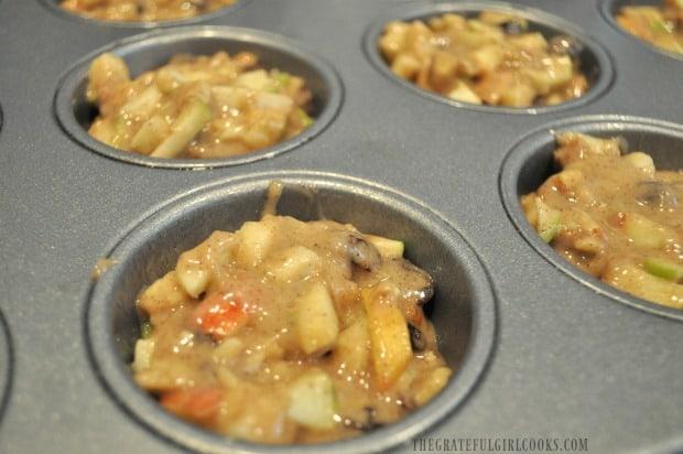 Apple raisin muffin batter in metal muffin tin