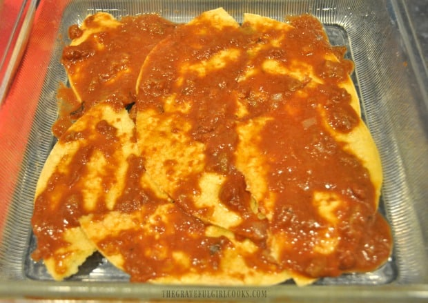 Enchilada/mole sauce is spread over tortillas