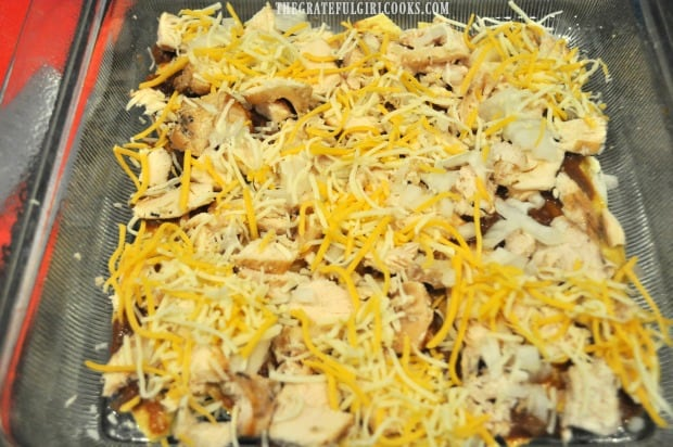 Chicken, onions and cheese layered onto enchilada casserole