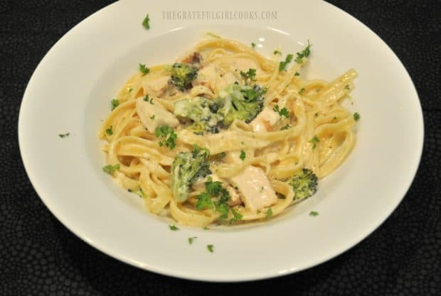 Chicken fettucine is garnished with parsley before serving