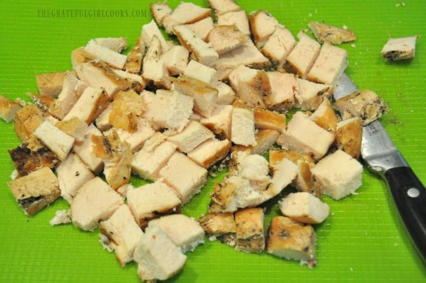 Cooked chicken breasts are cut into cubes before adding to alfredo sauce.