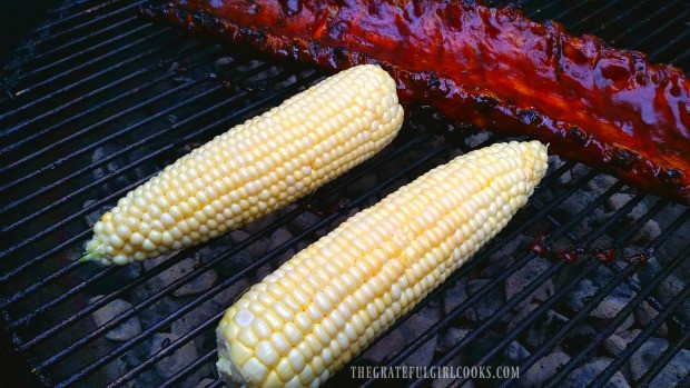 Corn is placed on hot BBQ grill to cook