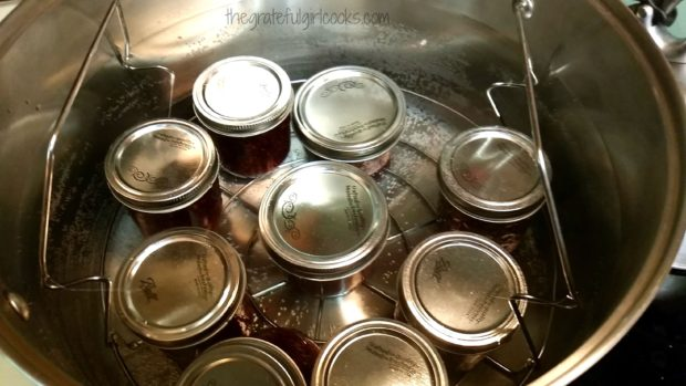 Jars of jam sit on a rack in water bath canner