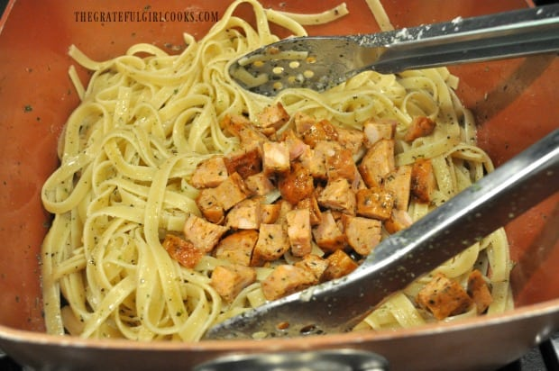 Cooked chicken Italian sausage pieces are tossed into seasoned pasta.