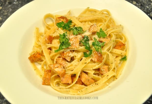 Chicken sausage pasta is garnished with parsley and Parmesan cheese.