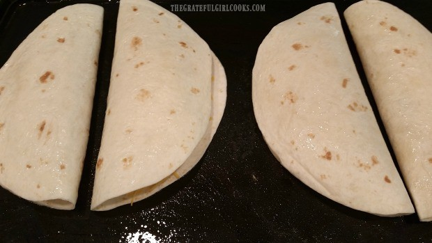 Each chicken black bean quesadilla is folded in half and place on griddle to cook.