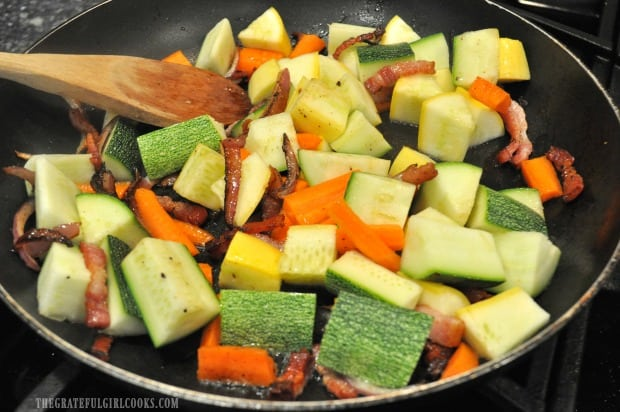 Summer squash and carrots are added to bacon sauté.