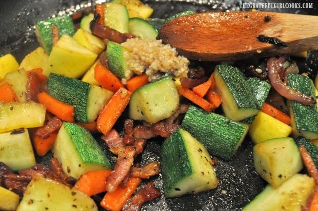 Minced garlic is added to sauteéd summer squash.