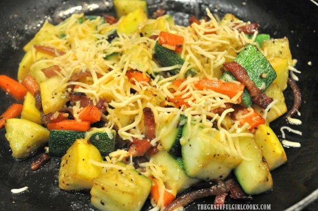 Grated cheddar cheese is added to the top of the summer squash.