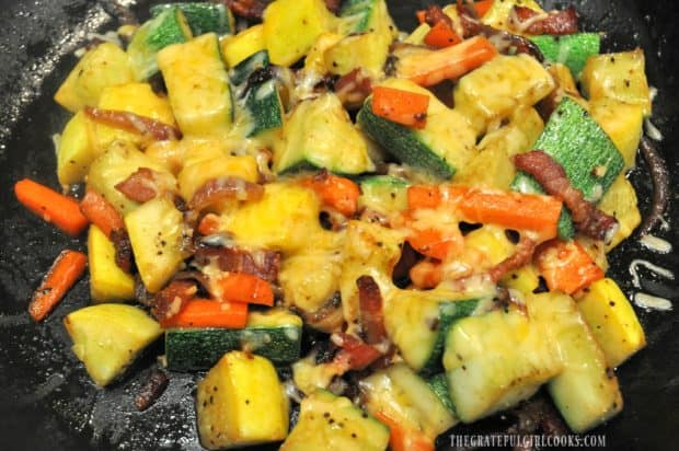 Cheddar cheese melts to top of the summer squash bacon sauté.