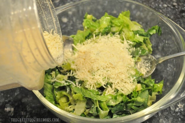 Shredded Parmesan cheese is added to caesar salad.