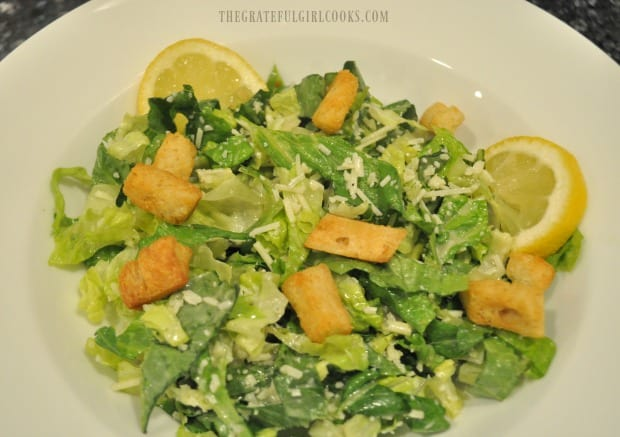 Croutons and lemon slices are added to caesar salad.