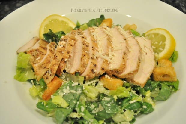Grilled chicken breast is sliced, then fanned out on top of caesar salad before serving.