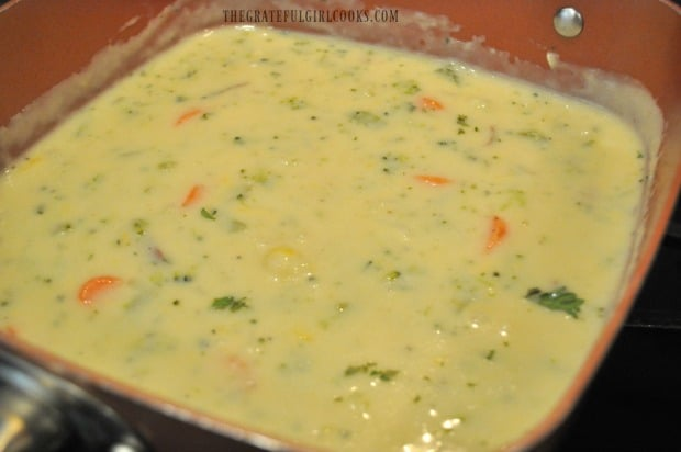 Cheese is mixed into the vegetable chowder until it has melted.