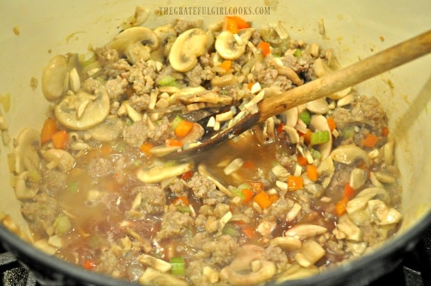 Chopped mushrooms, red wine, and broth are added to make ragu sauce.