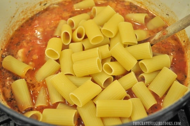 Rigatoni pasta is added to sausage musroom ragu sauce.