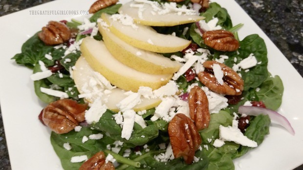 Candied pecans, goat cheese and sliced pear added to spinach salad.