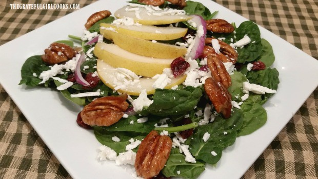 Spinach pear salad with candied pecans, on white plate.